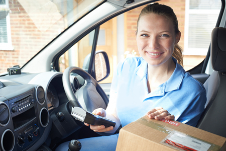 Portrait Of Female Courier In Van Delivering Package To Domestic House