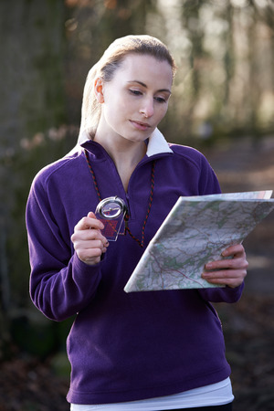 Woman Orienteering In Woodlands With Map And Compass Stock fotó
