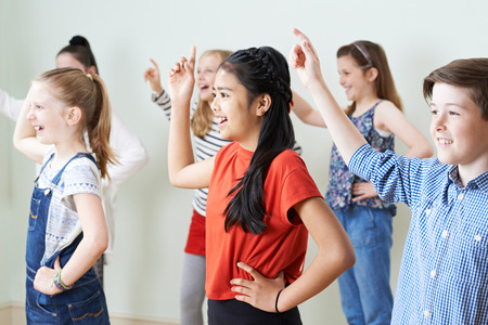 Group Of Children Dancing In Drama Class Together