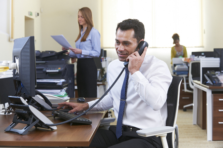 Businessman Making Phone Call At Desk In Busy Office