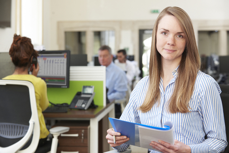 Portrait Of Businesswoman Studying Report In Busy Modern Office