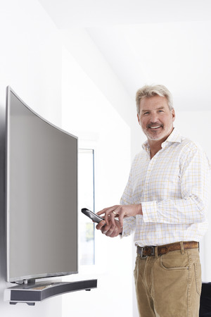 Portrait Of Mature Man With New Curved Screen Television At Home