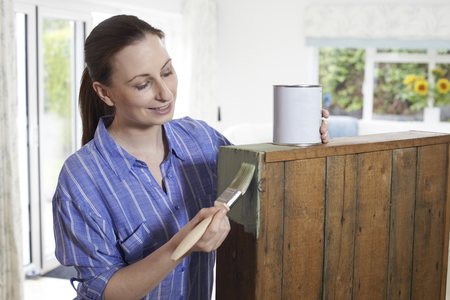 Woman Painting Old Wooden Cabinet At Home Stock Photo