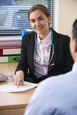 Female Doctor Having Discussion With Male Patient In Surgery