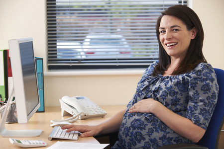 Portait Of Pregnant Businesswoman Working At Desk In Office