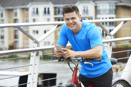 Portrait Of Man Using Mobile Phone Whilst Out On Cycle Ride Stock fotó