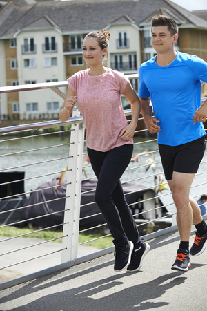 Young Couple Exercising In Urban Environment