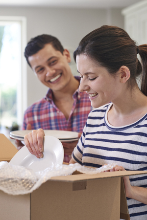 Young Couple Unpacking Boxes In Kitchen On Moving Day Stock fotó