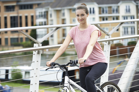 Portrait Of Young Woman Cycling Next To River In Urban Setting Stock fotó