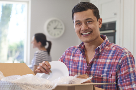 Portrait Of Young Couple Unpacking Boxes In Kitchen On Moving Day Stock fotó