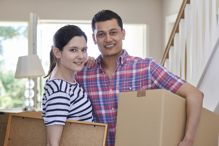 Portrait Of Couple Carrying Boxes Into New Home On Moving Day Stock fotó