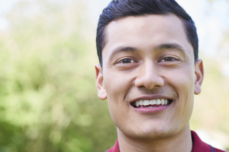Outdoor Head And Shoulders Portrait Of Smiling Young Man Stock fotó