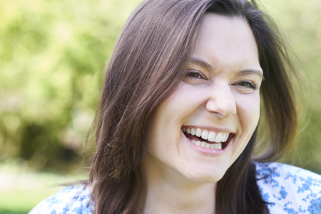 Outdoor Head And Shoulders Portrait Of Laughing Young Woman Stock fotó