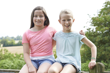 Portrait Of Two Girls Sitting On Gate Together Stock fotó