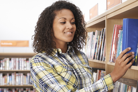 Female Student Choosing Book In Library