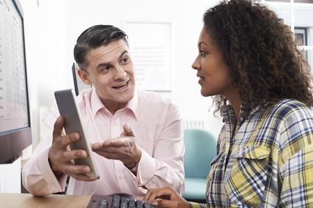 Man Training Woman In Office Using Digital Tablet Stock fotó