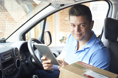 Portrait Of Courier In Van With Digital Tablet Delivering Package To House Stock fotó