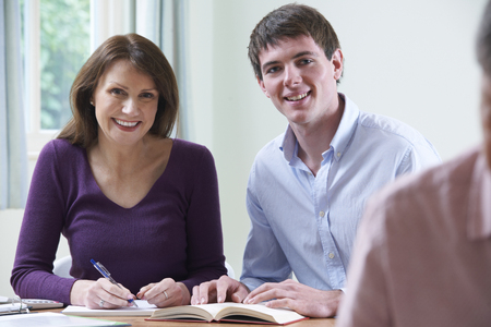 Portrait Of Mature Woman With Tutor In Adult Education Class