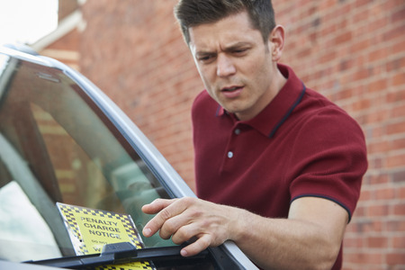 Frustrated Male Motorist Looking At Parking Ticket