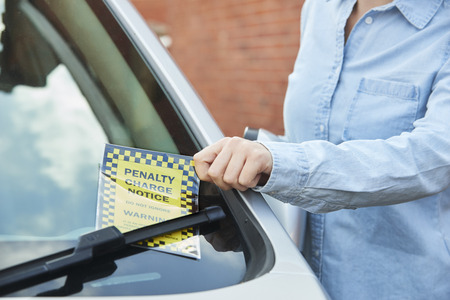 Close Up Of Female Motorist Looking At Parking Ticket