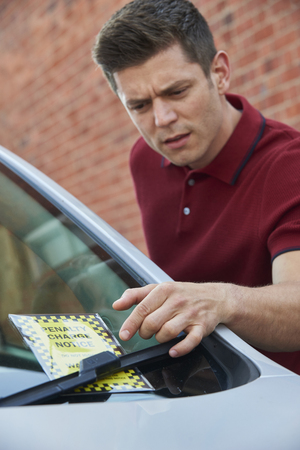Frustrated Male Motorist Looking At Parking Ticket Archivio Fotografico - 107807787