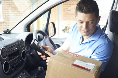 Courier In Van Delivering Package To Domestic House