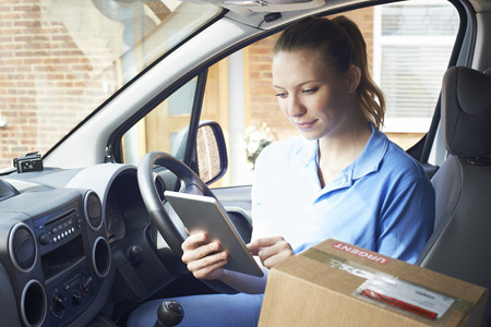 Female Courier In Van With Digital Tablet Delivering Package To House