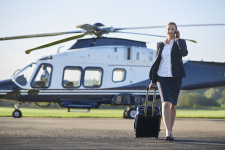 Businesswoman Walking Away From Helicopter Whilst Talking On Mobile Phone Stock fotó