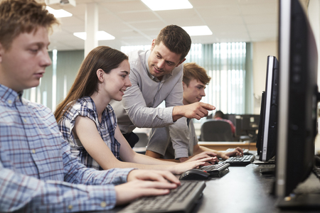 Teacher Helping Female High School Student Working In Computer Class