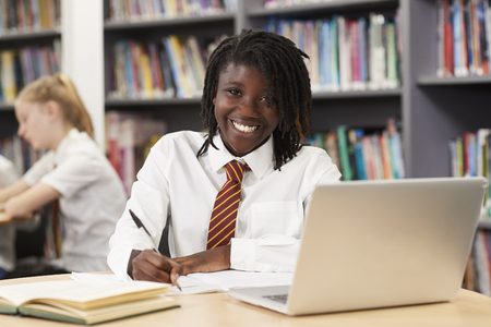 Portrait Of Female High School Student Wearing Uniform Working At Laptop In Library