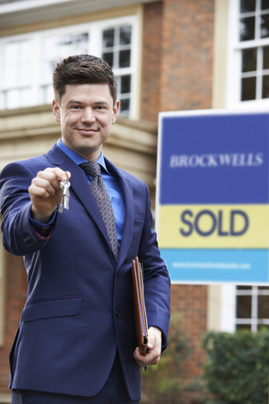 Portrait Of Male Realtor Standing Outside Residential Property Holding Keys