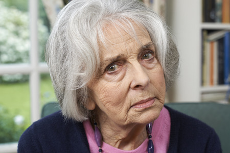 Head And Shoulders Portrait Of Unhappy Senior Woman At Home