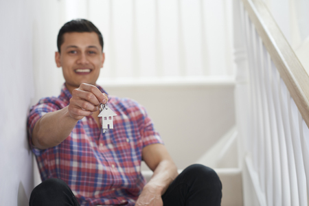 Young Man Sitting On Stairs Holding Keys To New Home