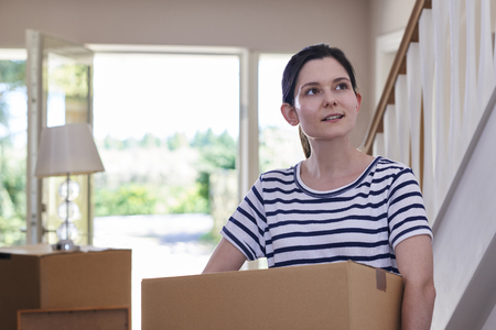 Young Woman Carrying Boxes Into New Home On Moving Day