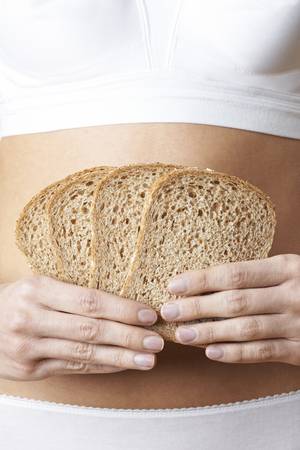Close Up Of Woman Wearing Underwear Holding Slices Of Brown Bread Stock Photo