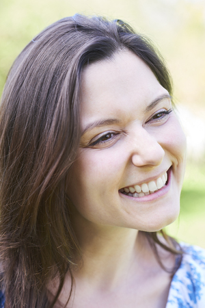 Outdoor Head And Shoulders Portrait Of Laughing Young Woman Stock Photo