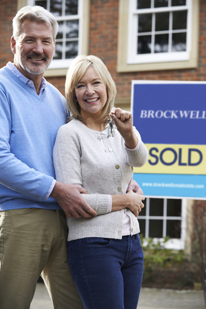 Portrait Of Mature Couple With Keys To New Home