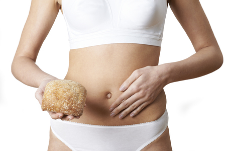 Close Up Of Woman Wearing Underwear Holding Bread Roll And Touching Stomach Stock Photo