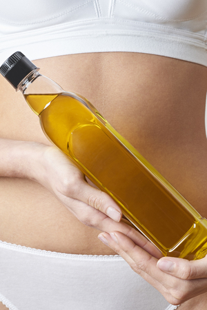 Close Up Of Woman In Underwear Holding Bottle Of Olive Oil