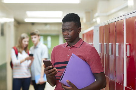 Portrait Of Male High School Student Bullied By Text Message In Corridor Stock Photo