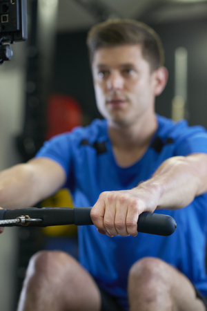 Man In Gym Exercising On Rowing Machine