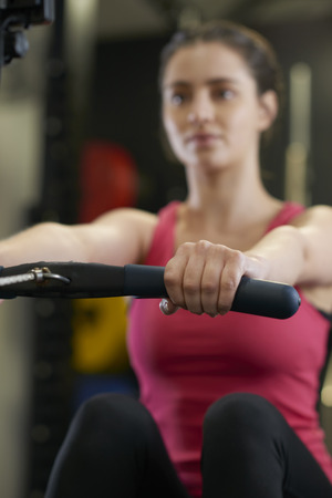 Young Woman In Gym Exercising On Rowing Machine