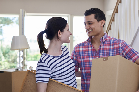 Young Couple Carrying Boxes Into New Home On Moving Day