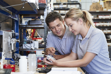 Engineer Helping Female Apprentice In Factory To Measure Component Using Micrometer Stock Photo