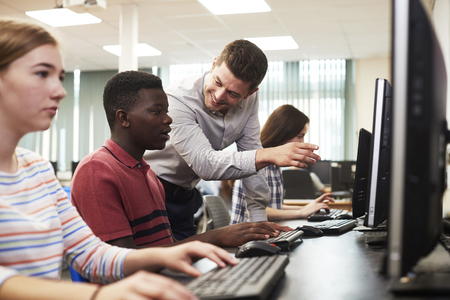 Teacher Helping Male High School Student Working In Computer Class Stock Photo