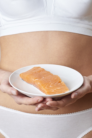 Close Up Of Woman In Underwear Holding Plate Of Salmon Stock Photo
