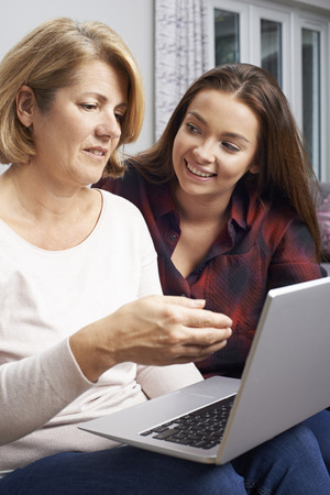 Teenage Daughter Showing Mother How To Use Laptop Computer Stock Photo