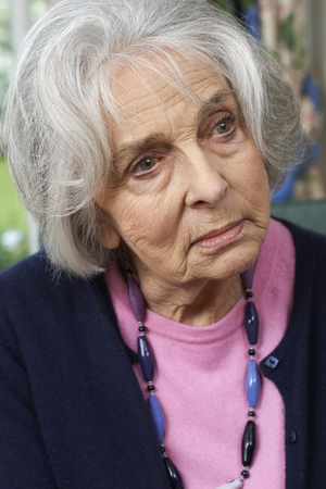 Head And Shoulders Shot Of Thoughtful Senior Woman At Home