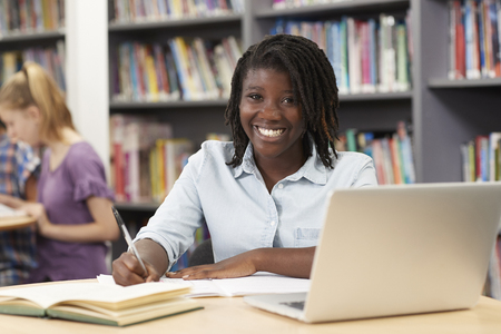 Portrait Of Female High School Student Working At Laptop In Library