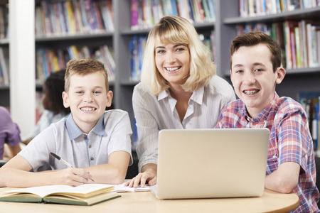 Portrait Of Female Teacher Helping Two Male High School Students Working At Laptop In Library Stock Photo